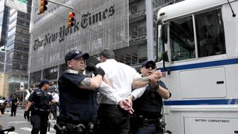 New York Police officers take into custody an activist during a climate change rally outside of the New York Times building, Saturday, June 22, 2019, in New York. Activists blocked traffic along 8th Avenue during a sit-in to demand coverage of climate change by the newspaper. (AP Photo/Julio Cortez)