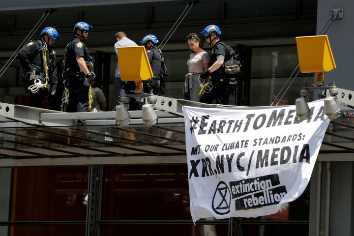 New York Police officers take into custody activists who climbed on the awning of the New York Times building to hang signs d
