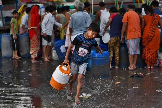 A boy carries a water container after filling it from a Delhi Jal Board tanker at Sanjay Colony in Okhla...
