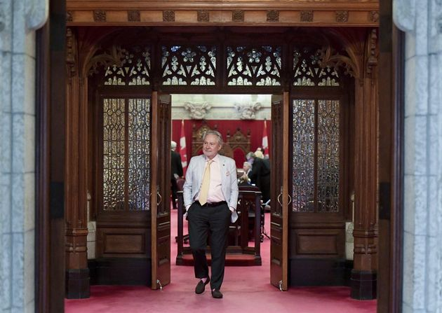 Sen. Peter Harder, the government representative in the Senate, leaves the chamber on June 19,