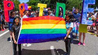 """PORTLAND, OR - JUNE 16:  Two girls lead a segment of the parade with a rainbow flag followed by adults with the word """"PRIDE"""" during the Portland Pride Parade and Festival on June 16, 2019, in Portland, OR. (Photo by Diego Diaz/Icon Sportswire via Getty Images)"""