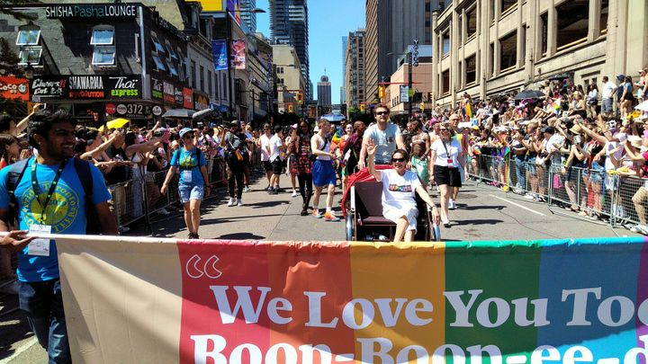 Sharon Hampson of Sharon and Bram sits in a rickshaw behind a banner at Toronto's Pride Parade on Sunday.