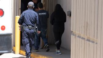 Recently apprehended migrants, like Yolanda (not pictured) are escorted inside the El Paso County detention facility by a Customs and Border Protection agent on June 12, 2019 in El Paso. - AFP presents a photo essay of 36 images by photographer Paul Ratje on the ordeal of Yolanda - who asked that we not use her last name - one of thousands of would-be migrants from Central American fleeing violence and seeking asylum in the United States who were told to wait for their court hearing in Mexico.  Yolanda came from El Salvador a little bit less than five months ago with her year-old grandson and teenage daughter and they were separated when they crossed the border from Mexico to the US. She now faces the opaque and dysfunctional US immigration system, with a kaleidoscope of legal requirements that even lawyers find hard to navigate, seeking asylum. There are almost 19,000 asylum seekers in Mexican border cities waiting for a US court hearing, according to research based on US and Mexican official figures. At least 5,000 of them are in Ciudad Juarez, El Paso's Mexican sister city. (Photo by Paul Ratje / AFP)        (Photo credit should read PAUL RATJE/AFP/Getty Images)