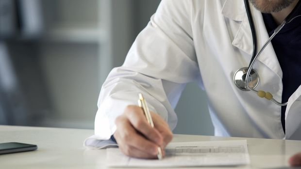 Experienced physician completing health insurance claim form, healthcare