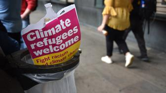 "LONDON, ENGLAND - MAY 24: A placard saying ""Climate refugees welcome"" is left in a bin after students take part in a Climate rally in Parliament Square on May 24,, 2019 in London, United Kingdom. Students continue to stage protests, urging the government to declare a climate emergency and take action over the problem. They are keen that the national curriculum is reformed and the environmental crisis is communicated to the public. (Photo by John Keeble/Getty Images)"