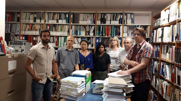 Staff at the Injured Workers Community Legal Clinic pose for a photo at their office. Each pile of documents...
