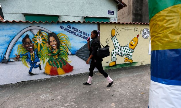 A woman walks past graffiti depicting Brazilian football superstars Pelé, left, and Marta, right,...