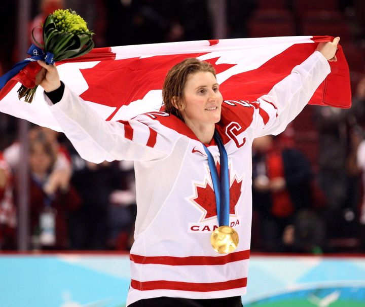 Hayley Wickenheiser hoists the Canadian flag after winning Gold at the 2010 Winter Olympics in Vancouver.