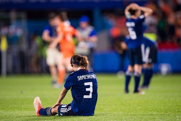 芝生の上に座り込む、鮫島選手
