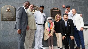 Representatives of the the Stonewall Inn and the New York Yankees, including pitcher CC Sabathia, third from left; relief pitcher Dellin Betances, second from right; assistant general manager Jean Afterman, center; and general manager Brian Cashman, right, honor the 50th anniversary of the Stonewall Inn Uprising after the Yankees unveiled a plaque in Monument Park before a baseball game Tuesday, June 25, 2019, in New York. Stonewall witness Tree Sequoia, second from left, and Stonewall owner co-owner Kurt Kelly, third from right, in front of Betances, joined the group. (AP Photo/Kathy Willens)