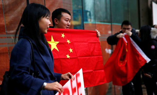 A man holds a Chinese flag outside the B.C. Supreme Court bail hearing of Huawei CFO Meng Wanzhou in...