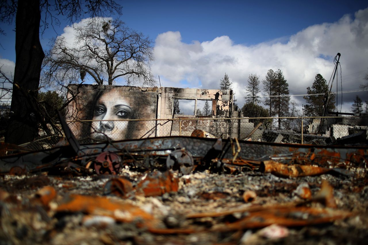 A mural by artist Shane Grammer is visible on the wall of a building destroyed by the 2018 wildfire that destroyed the town of Paradise, California. Climate change is leading to more intense and more frequent wildfires.