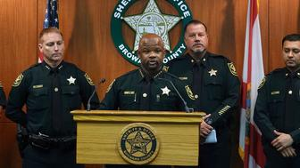 Broward Sheriff Gregory Tony, center, announces that two additional deputies have been fired as a result of the agency's internal affairs investigation into the mass shooting at Marjory Stoneman Douglas High School in Parkland, at the Broward Sheriff's Office headquarters in Fort Lauderdale, Fla., Wednesday, June 26, 2019. Tony said deputies Edward Eason and Josh Stambaugh were fired Tuesday for their inaction following the Feb. 14, 2018 shooting.  (Joe Cavaretta/South Florida Sun-Sentinel via AP)