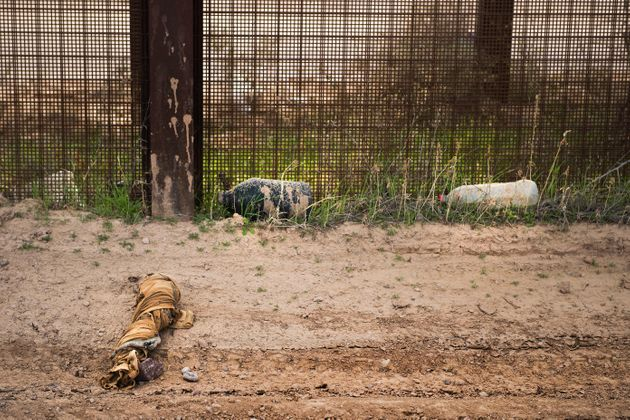 Aswath of fabric and empty water jugs lay next to the border fence outside Lukeville, Arizona,...