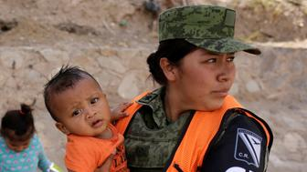 A member of the National Guard holds a boy of a Honduran migrant after she and her children were stopped from crossing illegally into El Paso, Texas, United States, in Ciudad Juarez, Mexico June 26, 2019. REUTERS/Jose Luis Gonzalez