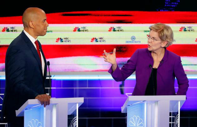 Sen. Elizabeth Warren talks with Sen. Cory Booker during the first Democratic primary debate. The 2020...
