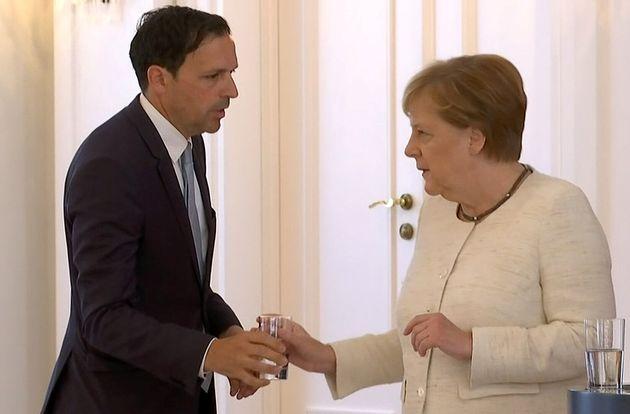 Angela Merkel recibe un vaso de agua, tras sufrir nuevos temblores durante un acto