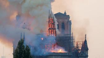 Smoke rises from the burning spire on the roof at the Notre-DameCathedral after a fire broke out, in Paris, France April 15, 2019. Picture taken April 15, 2019.  REUTERS/Charles Platiau