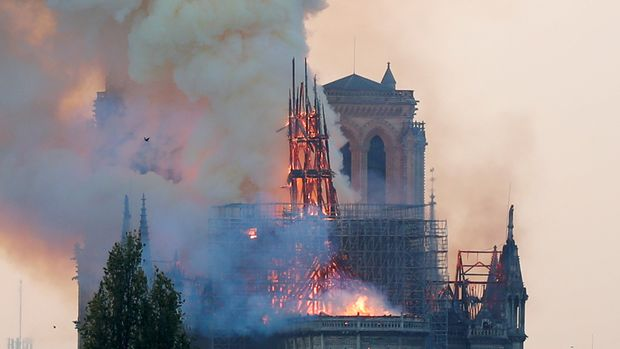 Smoke rises from the burning spire on the roof at the Notre-Dame Cathedral after a fire broke out, in Paris, France April 15, 2019. Picture taken April 15, 2019.  REUTERS/Charles Platiau