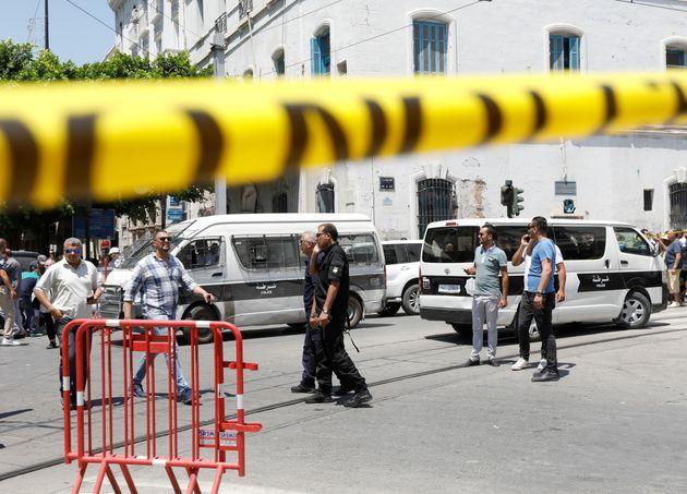 Un grupo de agentes y civiles, en el lugar donde se ha producido el ataque contra el convoy