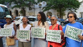 Rep. Ayanna Pressley (D-Mass.), center, holds up signs with supporters that call for Harriet Tubman to be put on the $20 bill at a press conference on Thursday June 27, 2019.