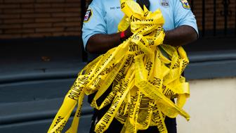 An officer removes crime scene tape after the investigation of what police say was a shooting with one victim in Philadelphia, Wednesday, June 19, 2019. (AP Photo/Matt Rourke)