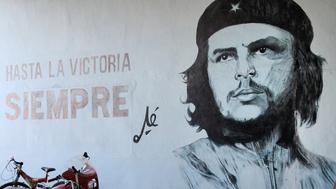 Tourist stands next to wall mural with revolution propaganda on February 22, 2011 in Sancti Spiritus, Cuba. Revolution propaganda is promoted by national government.