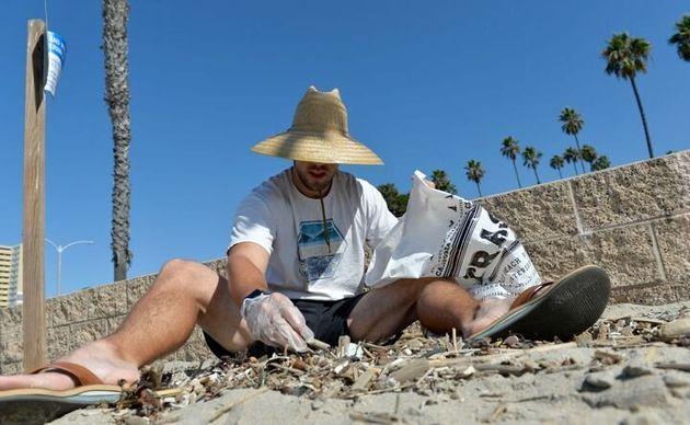 カリフォルニアのロングビーチで、瓦礫の中からタバコの吸い殻を選んで拾うボランティア