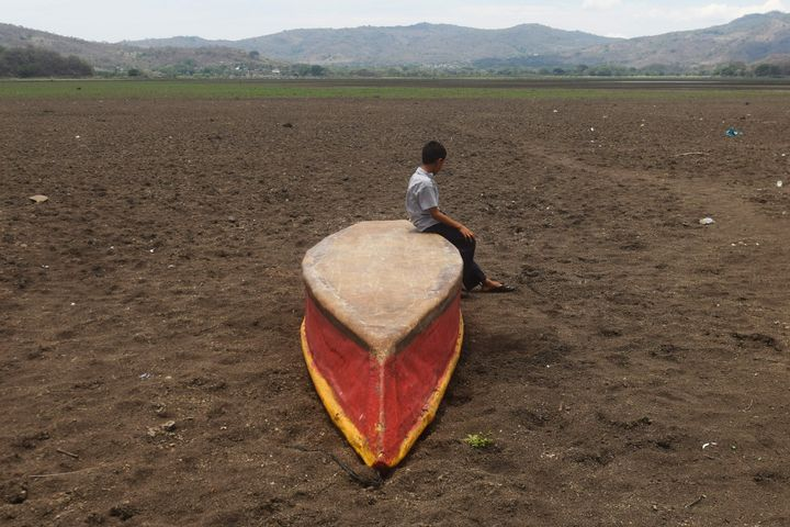 A boy sits on an abandoned boat on what is left of drought-parched Lake Atescatempa in Guatemala.