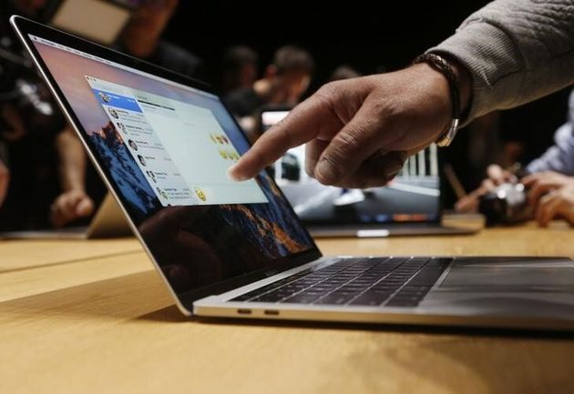 This photo from 2016 shows an Apple user pointing at the screen of a 15-inch MacBook Pro at a media event...
