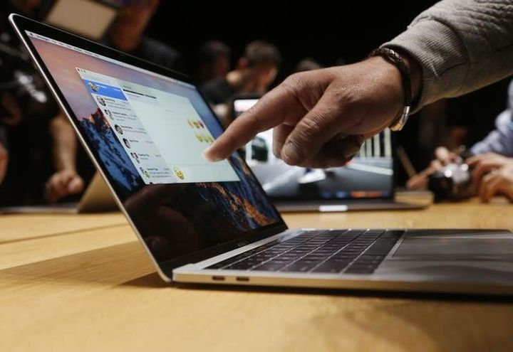 This photo from 2016 shows an Apple user pointing at the screen of a 15-inch MacBook Pro at a media event in California.