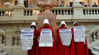 Women hold signs to protest HB 481 at the state Capitol, Tuesday, April 2, 2019, in Atlanta. HB 481, which would ban most abortions after a fetal heart beat is detected, has past both the House and the Senate and awaits a signature from Gov. Brian Kemp. (AP Photo/John Bazemore)