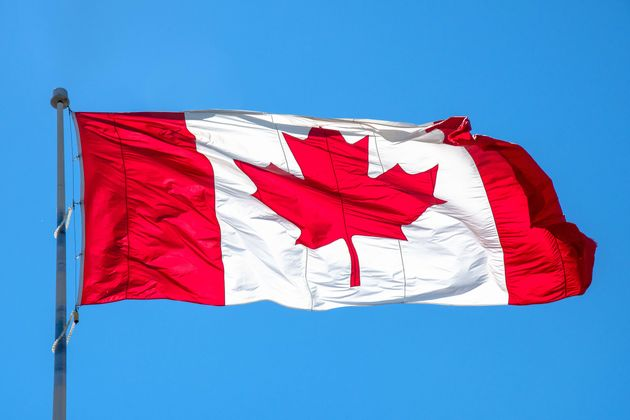 This photo shows a Canadian flag flying over Toronto under a clear blue sky in July