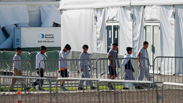 "FILE - In this Feb. 19, 2019 file photo, children line up to enter a tent at the Homestead Temporary Shelter for Unaccompanied Children in Homestead, Fla. Immigrant advocates say the U.S. government is allowing migrant children at a Florida facility to languish in ""prison-like conditions"" after crossing the U.S.-Mexico border instead of releasing them promptly to family as required by federal rules. A court filing Friday, May 31, 2019 revealed conditions inside the Homestead, Florida, facility that has become the nation's biggest location for detaining immigrant children. (AP Photo/Wilfredo Lee, File)"