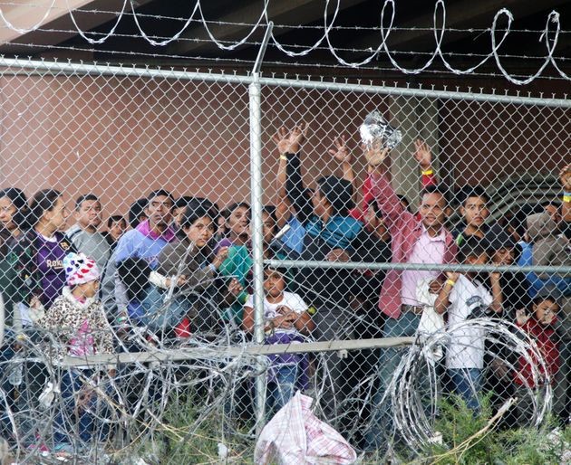 Central American adults and children stand imprisoned in a pen erected by U.S. Customs and Border Protection...