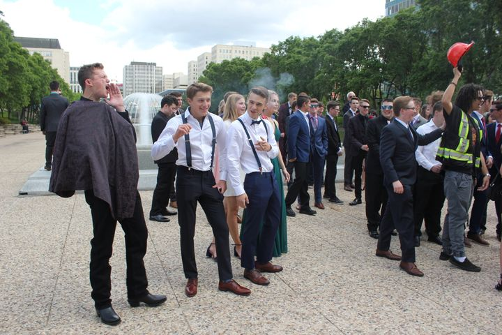 Graduating high school students yell at climate protesters gathered on Alberta's legislature grounds.