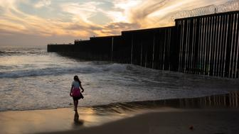 A girl plays along the border wall, right, separating San Diego from Tijuana, Mexico, where it meets the Pacific Ocean, Tuesday, June 11, 2019, in Tijuana. A centerpiece of a new immigration agreement between Mexico and the United States calls for rapid expansion of a policy that makes Central American asylum seekers wait in Mexico while their cases wind through U.S. immigration courts. (AP Photo/Gregory Bull)