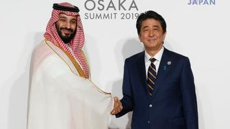 Saudi Arabia's Crown Prince Mohammed bin Salman (L) is welcomed by Japanese Prime Minister Shinzo Abe upon his arrival for a family photo session at the G20 Summit in Osaka on June 28, 2019. (Photo by KIM KYUNG-HOON / POOL / AFP)        (Photo credit should read KIM KYUNG-HOON/AFP/Getty Images)