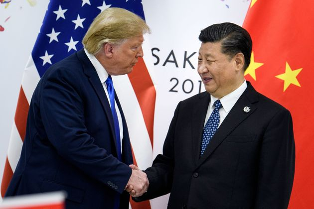 China's President Xi Jinping shakes hands with US President Donald Trump before a bilateral meeting at...