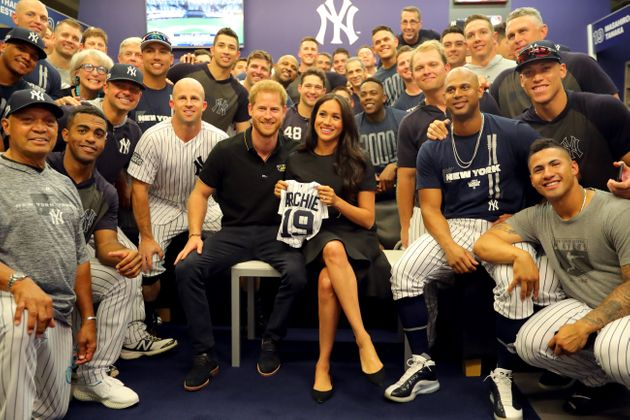 The Duke and Duchess of Sussex pose for a photo with the New York Yankees in the clubhouse prior to the...