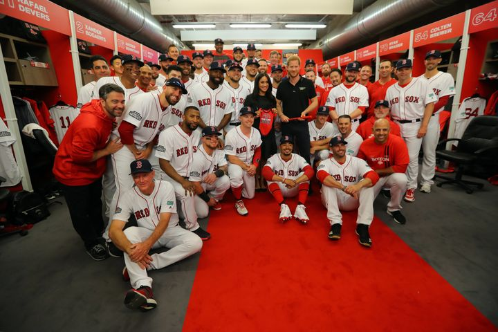 Meghan Markle and Prince Harry pose for a photo with the Red Sox in the clubhouse prior to the game.