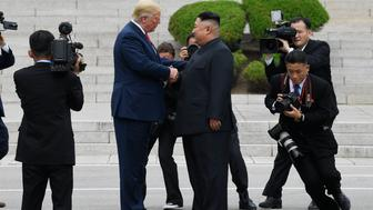 President Donald Trump walks to the North Korean side of the border with North Korean leader Kim Jong Un at the border village of Panmunjom in the Demilitarized Zone, Sunday, June 30, 2019, in North Korea. (AP Photo/Susan Walsh)