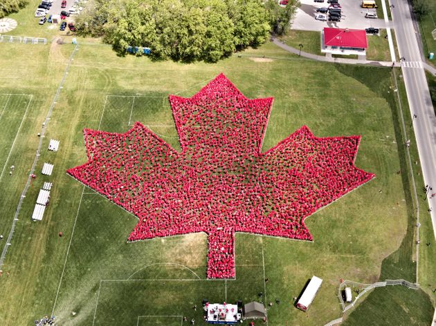 People wear red to form a giant maple leaf in Trenton, Ont. on
