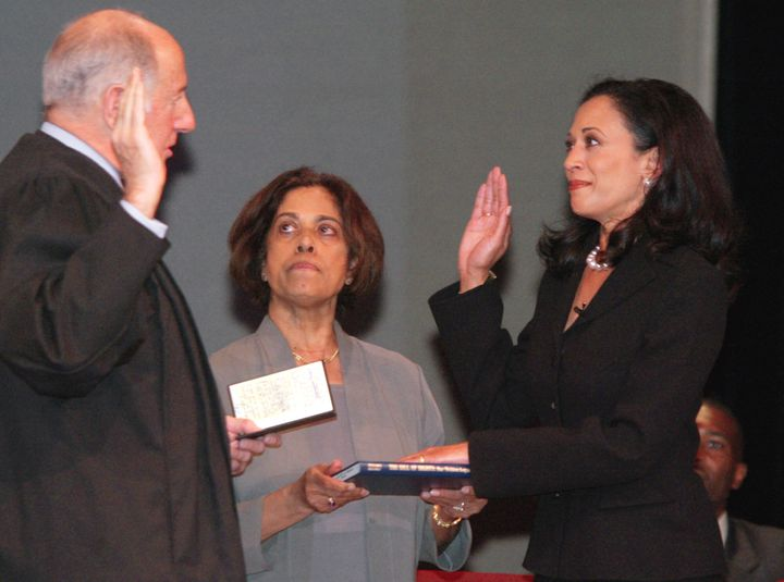 "Kamala Harris, right, receives the oath of office on Jan. 8, 2004, in San Francisco. In the center is Harris' mother, Dr. Shyamala Gopalan, who holds a copy of ""The Bill of Rights."""