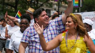 Gov. J. B. Pritzker, center, participates in the 50th Chicago Pride Parade in Chicago, Sunday, June 30, 2019. (AP Photo/Amr Alfiky)