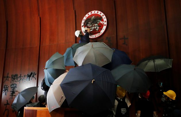 A person sprays paint over Hong Kong's coats of arms inside a chamber after protesters broke into the...