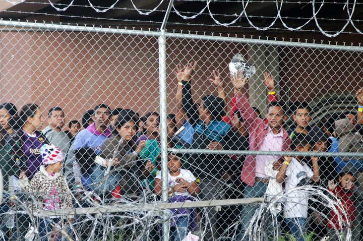 In this March 27, 2019, file photo, Central American migrants wait for food in a pen erected by U.S. Customs and Border Prote