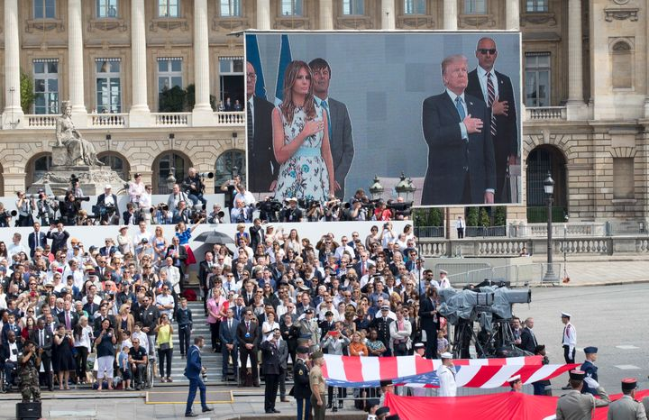 President Donald Trump and first lady Melania Trump are seen on a large screen as they stand during the U.S. national anthem