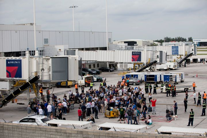People stand on the tarmac at the Fort Lauderdale-Hollywood International Airport after a shooter opened fire inside a termin