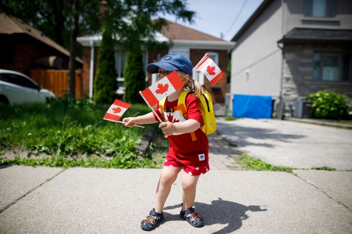 "This little reveller, Blair, is just two years old, but is already maximizing her flag-and-maple-leaf capacity. And it looks like her hat has a ""6"" on it, perhaps repping Toronto?"
